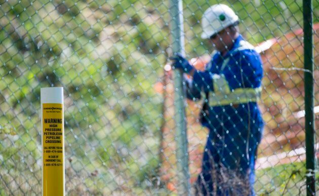 A worker installs new fence posts surrounding the Burnaby, B.C. Kinder Morgan location on April 26,