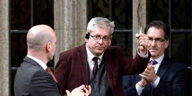 NDP MP Charlie Angus holds a feather as he rises to vote in favour of the NDP's motion calling on the...