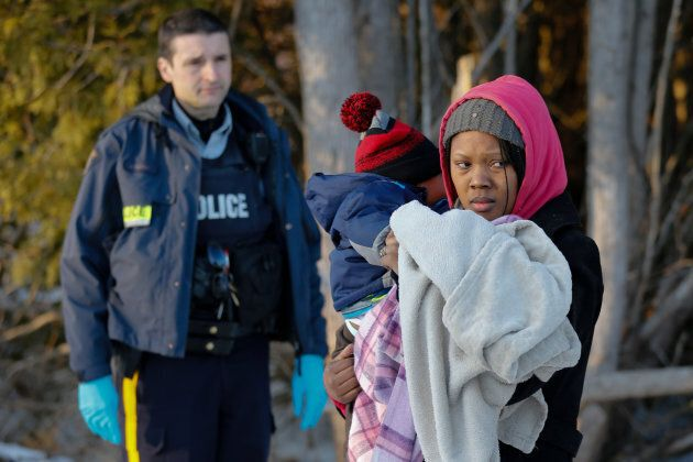 A Royal Canadian Mounted Police officer looks on as a woman carrying a child waits to cross the border...