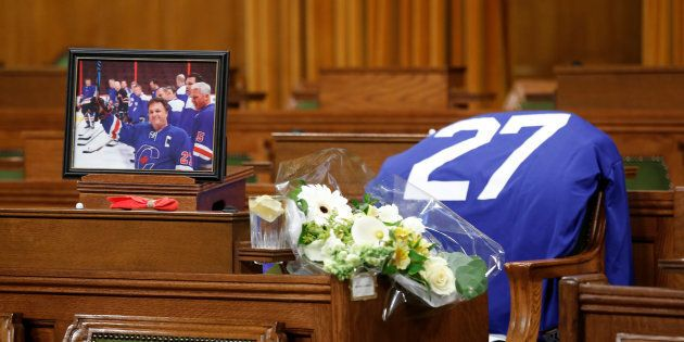 Flowers, a photograph and a hockey jersey are seen at the desk of the late Conservative MP Gord Brown, who died Wednesday, in the House of Commons on May 2, 2018.
