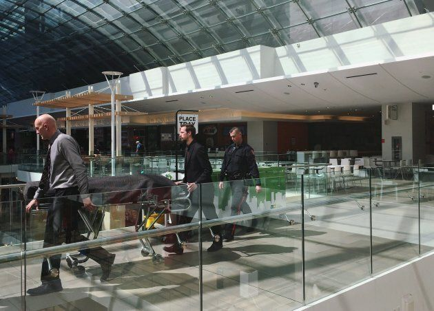 Medical examiners escort a body found in a wall in the women's washroom in the Core Shopping Centre in...