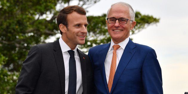 French President Emmanuel Macron embraces Australian Prime Minister Malcolm Turnbull (R) at the end of a joint press conference in Sydney on May 2, 2018.