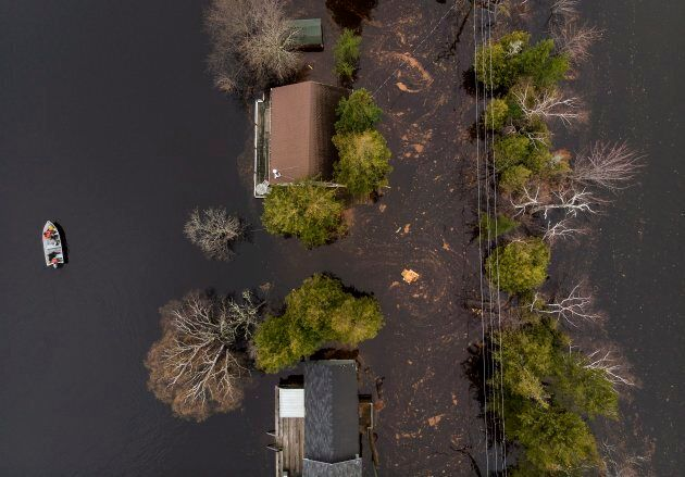A boat drives next to cottages and homes along a flooded roadway on Grand Lake, N.B. as floodwaters continue...