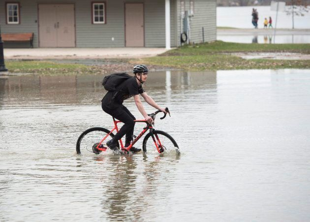 Stefan Curtis rides his bike through the flood water in Officers Square in Fredericton, New Brunswick...
