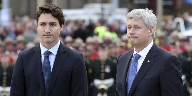 Stephen Harper and Justin Trudeau pause after laying a wreath during a ceremony to commemorate the October 2014 attack on Parliament Hill, at the National War Memorial in Ottawa on Oct. 22, 2015.