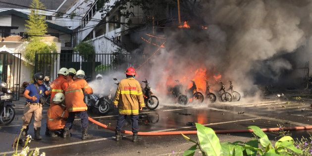 Firefighters try to extinguish a blaze following a blast at the Pentecost Church Central Surabaya in...