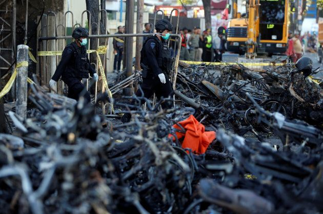 Members of the Indonesian Special Forces Police counter-terrorism squad walk by burned motorcycles following...