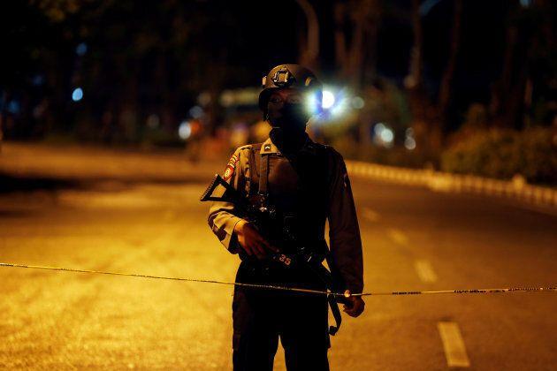 An Indonesian policemen guard at a street following a blast at the Pentecost Church Central Surabaya,...