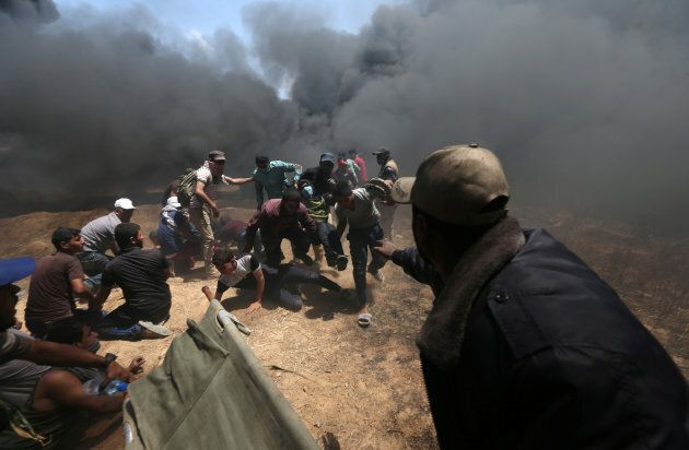 A wounded Palestinian demonstrator is evacuated as others take cover from Israeli fire and tear gas during...