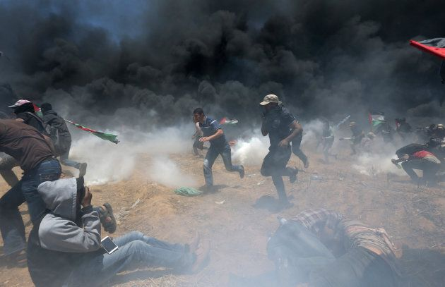Palestinian demonstrators run for cover from Israeli fire and tear gas during a protest against U.S....