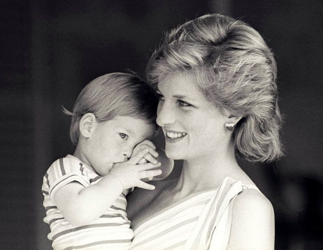 Princess Diana holds Prince Harry during a morning picture session at Marivent Palace, where the Prince...
