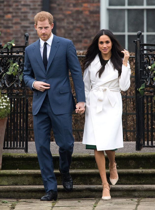 Meghan Markle, wearing a white belted coat by Canadian brand Line, attends a photocall at Kensington Palace with Prince Harry.
