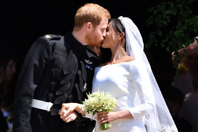 Prince Harry kisses his wife Meghan as they leave from the West Door of St George's Chapel, Windsor Castle,...
