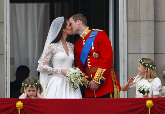 Prince William and Kate Middleton kiss on the balcony of Buckingham Palace, London.