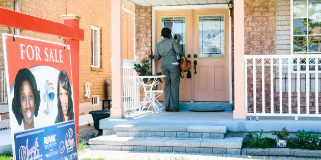 A real estate agent stands outside of a home holding an open house in Brampton, Ont., near Toronto, Sat....