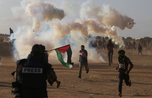 Palestinian demonstrators run from tear gas fired by Israeli troops during a protest marking the 70th...