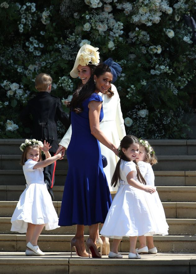 The Duchess of Cambridge and Canadian stylist Jessica Mulroney hold bridesmaids hands as they arrive for the wedding.