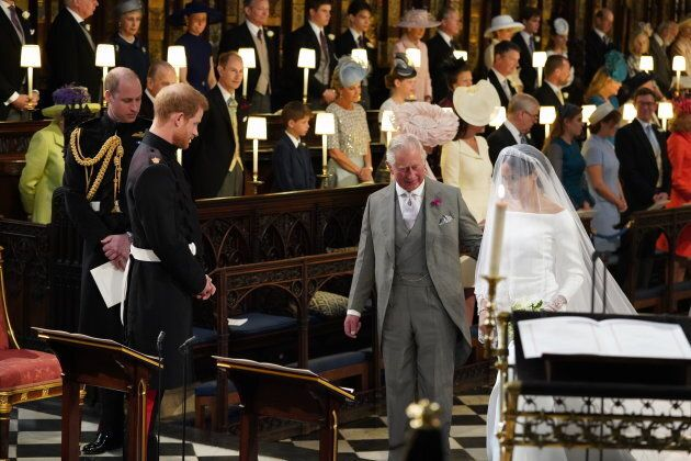 Prince Harry looks at his bride, Meghan Markle, as she arrives accompanied by Prince Charles, Prince of Wales during their wedding.