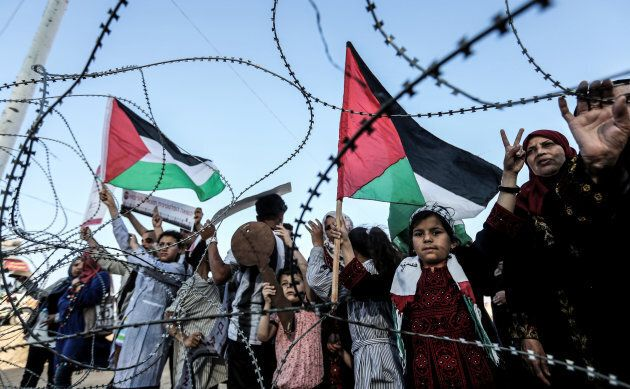 A girl raises a Palestinian flag as another Palestinian boy holds a wooden key symbolising the return,...