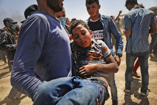 A child overcome by tear gas is rushed to medics at the border fence with Israel as mass demonstrations...