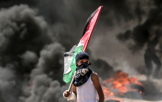 A Palestinian boy holding his national flag looks at clashes with Israeli security forces near the border...