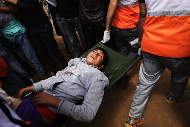 A wounded Palestinian boy is rushed to an ambulance at the border fence with Israel as mass demonstrations...