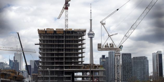 The CN Tower stands behind a condominium building under construction in Toronto on May 10. New home sales...