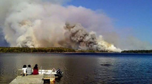People from the Paungassi First Nation watch a fire burning in Little Grand Rapids, Man. in a handout...