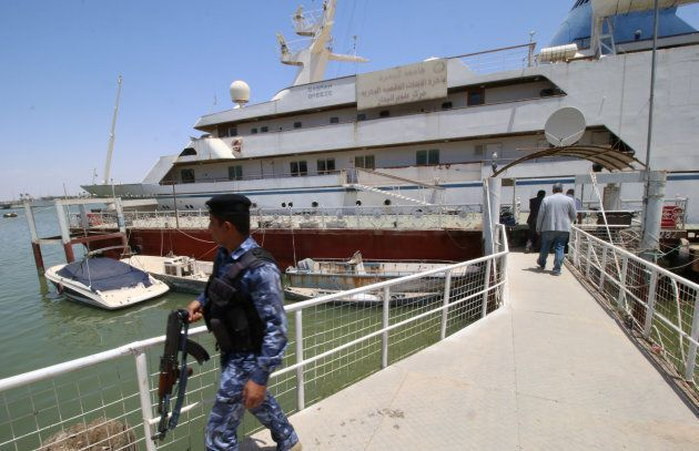 An Iraqi policeman walks past the yacht called