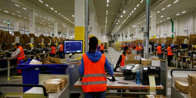 Workers handle items for delivery at an Amazon distribution center near Berlin, Germany, Nov. 28, 2013....