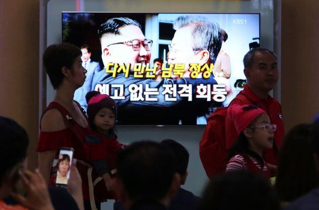 People watch a TV screen showing South Korean President Moon Jae-in, right, meets with North Korean leader...