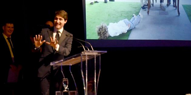 Prime Minister Justin Trudeau shows a slideshow of his trip to India as he jokes during his speech at...