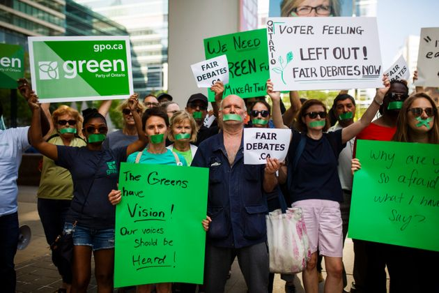 Ontario Green party supporters hold signs ahead of the Ontario Elections Leaders debate at the CBC building...
