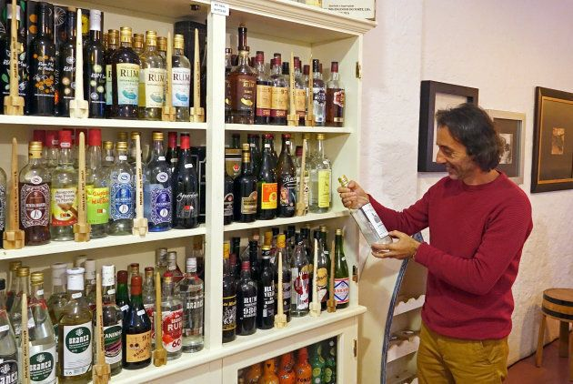 Roberto Andrade, who runs the Madeira Rum House, poses with his collection of rums in Funchal, Portugal,...