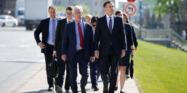 Finance Minister Bill Morneau (right) and Natural Resources Minister Jim Carr walk to a news conference...