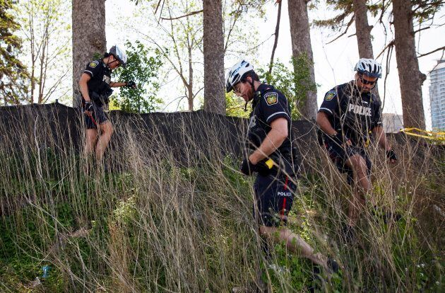 Police search around a wooded section near the scene of an explosion at a restaurant in Mississauga,...