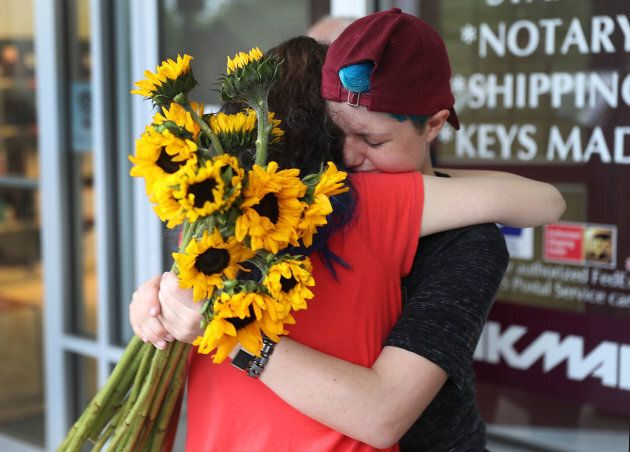 Caspen Becher (R) a freshman at Marjory Stoneman Douglas High School is hugged as she joins with others...
