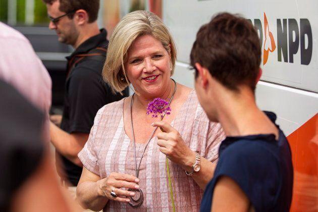 Ontario NDP leader Andrea Horwath holds a flower as she speaks Sarnia-Lambton NDP candidate Kathy Alexander...