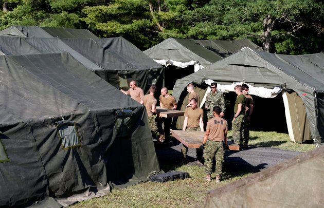 Members of the Canadian Armed Forces carry wooden flooring into the tents they erected to house asylum...