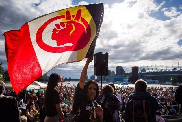 A woman holds a flag during a protest against the Kinder Morgan Trans Mountain Pipeline expansion in...