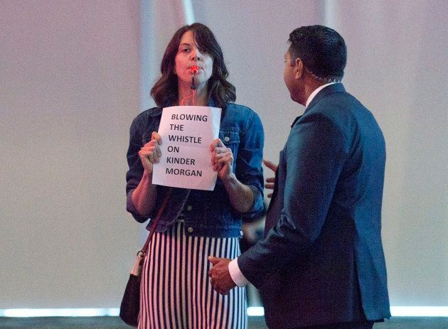 A protester, carrying a sign and blowning a whistle, disrupts Prime Minister Justin Trudeau's keynote...