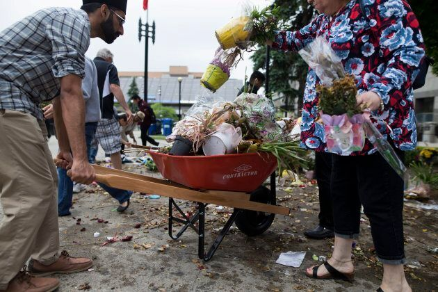 People dispose of dead flowers to mark the end of a makeshift memorial for victims of the Toronto van...