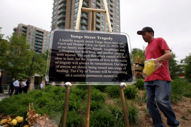 A plaque temporarily marks the site as people dispose of dead flowers to mark the end of a makeshift...