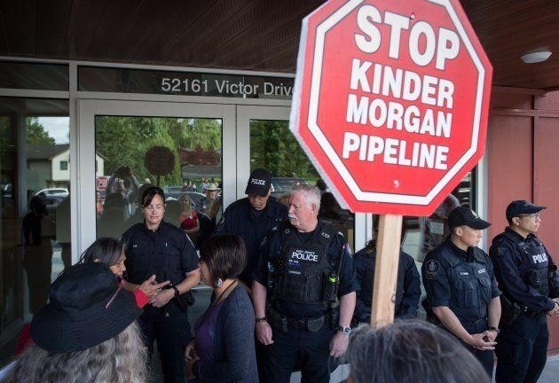 Denise Douglas of the Cheam First Nation, argues with a woman front of police officers as she demands...