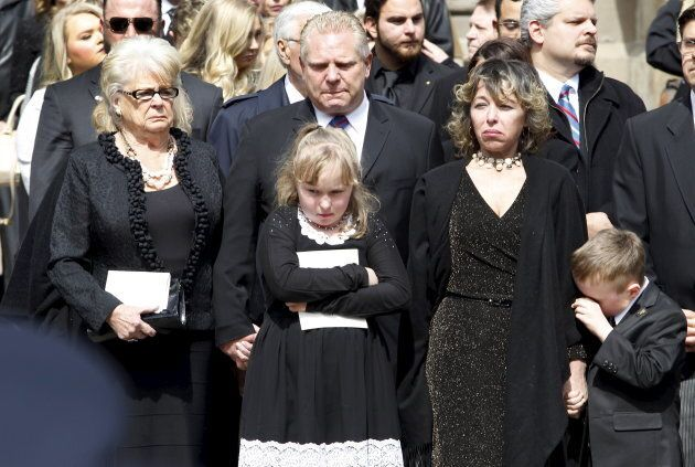 Renata Ford her daughter Stephanie and son Doug Ford Junior stand outside St James Cathedral with Doug Ford and his mother as the hearse leaves carrying former mayor Rob Ford, in Toronto on March 30, 2016.