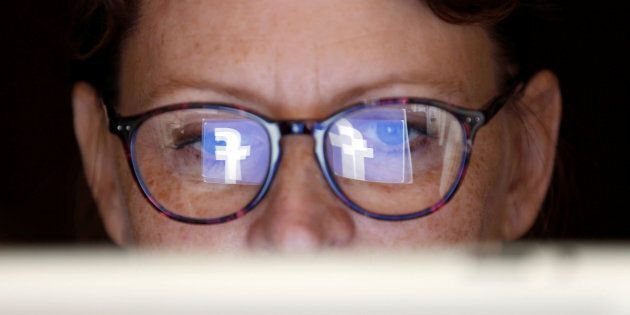 The Facebook logo is reflected on a woman's glasses in this photo illustration taken June 3,