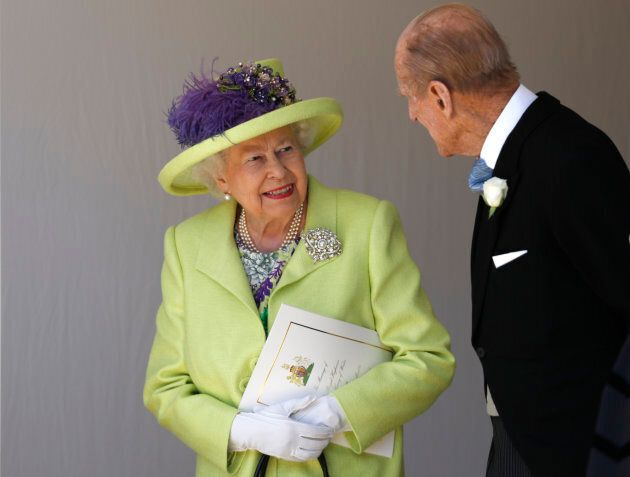 Queen Elizabeth II talks with Prince Philip as they leave the wedding ceremony of Prince Harry and Meghan...