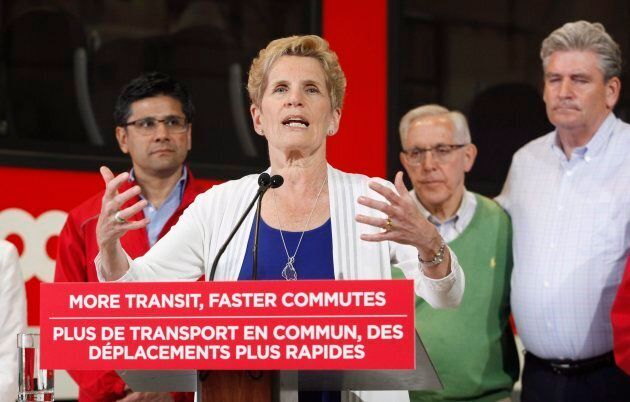 Ontario Liberal leader Kathleen Wynne speaks in front of the O-Train at a campaign stop in Ottawa on...
