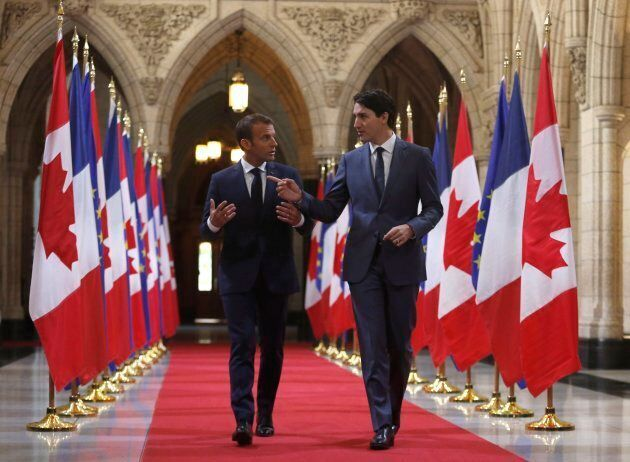 Prime Minister Justin Trudeau and French President Emmanuel Macron walk down the Hall of Honour on Parliament...