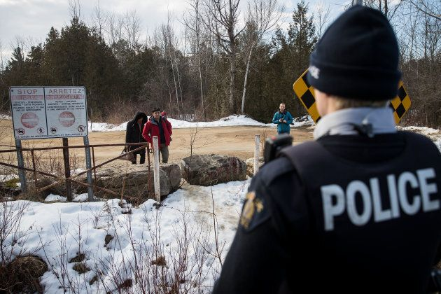 A couple claiming to be from Turkey is warned by a Royal Canadian Mounted Police officer before they cross the U.S.-Canada border into Canada on Feb. 23, 2017 in Hemmingford, Que.